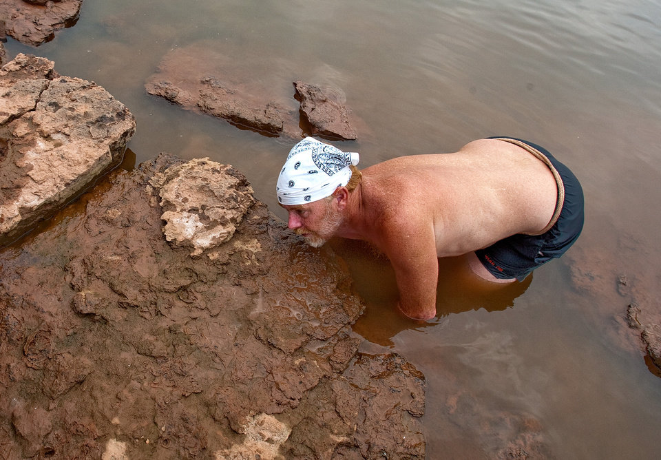 Lee McFarlin puts his hand into a catfish den. Lee McFarlin tries to catch catfish with his bare hands in the Cimarron River outside of Ripley, Okla., on Friday July 2, 2010. Photo by Mitchell Alcala, The Oklahoman