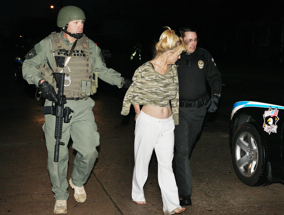 Agents with the Oklahoma Bureau of Narcotics and Dangerous Drugs Control and the Oklahoma County Sheriff Department arrest Pamela Millus on Wednesday at 3312 NW 25 in Oklahoma City. Photo by Paul B. Southerland, The Oklahoman <strong>PAUL B. SOUTHERLAND - PAUL B. SOUTHERLAND</strong>