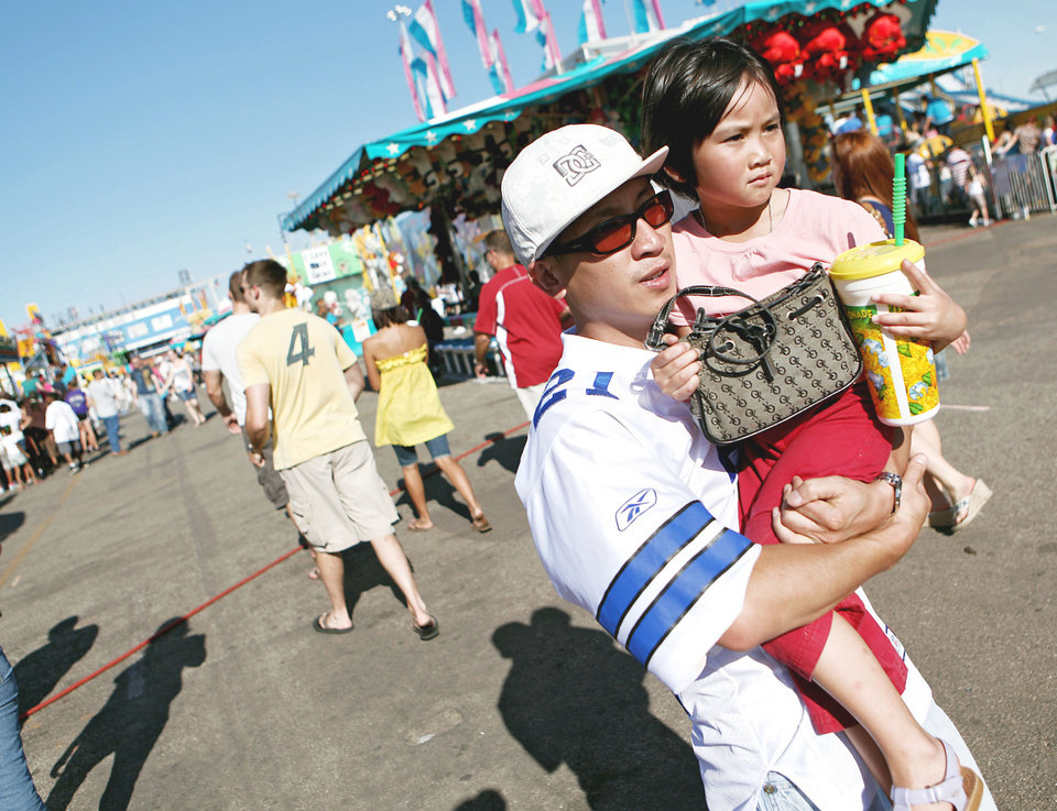 Photo - Jay Chan of Oklahoma City carries his niece, Christine Somsack,  4, through the midway Sunday  at the  Oklahoma State Fair.  Photo By  John Clanton,  The Oklahoman