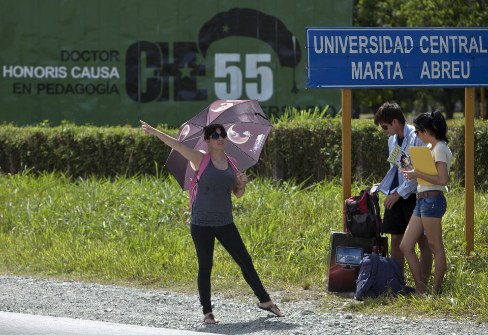 """Photo - In this July 11, 2014, photo, a Cuban student tries to flag down a taxi at the exit of Marta Abreu Central University in Santa Clara, Cuba. Beginning as early as October 2009, a project overseen by the U.S. Agency for International Development sent Venezuelan, Costa Rican and Peruvian nationals to Cuba to cultivate a new generation of political activists. Often posing as tourists, the young travelers befriended Cuban students. Fernando Murillo, contracted to turn politically apathetic young Cubans into """"change agents,"""" headed to Santa Clara and connected with a cultural group that called itself """"Revolution."""" (AP Photo/Franklin Reyes)"""