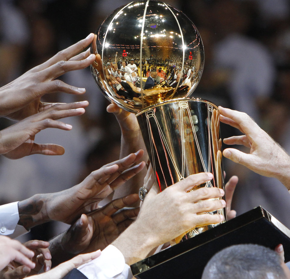 The Miami team reaches for the Larry O'Brien NBA Championship Trophy after Game 5 of the NBA Finals between the Oklahoma City Thunder and the Miami Heat at American Airlines Arena, Thursday, June 21, 2012. Oklahoma City lost 121-106. Photo by Bryan Terry, The Oklahoman