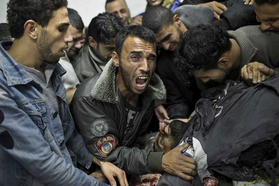 A Palestinian man cries next the body of a dead relative in the morgue of Shifa Hospital in Gaza City, Sunday, Nov. 18, 2012. President Barack Obama on Sunday defended Israel\'s airstrikes on the Gaza Strip, but he warned that escalating the offensive with Israeli ground troops could deepen the death toll and undermine any hope of a peace process with the Palestinians. (AP Photo/Bernat Armangue)