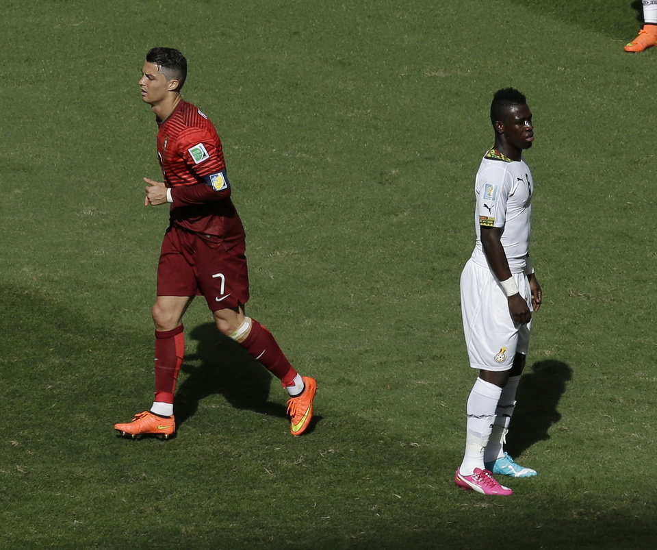 Photo - Portugal's Cristiano Ronaldo, left, runs past Ghana's Afriyie Acquah, right, after Ronaldo scored his side's 2nd goal during the group G World Cup soccer match between Portugal and Ghana at the Estadio Nacional in Brasilia, Brazil, Thursday, June 26, 2014. (AP Photo/Themba Hadebe)