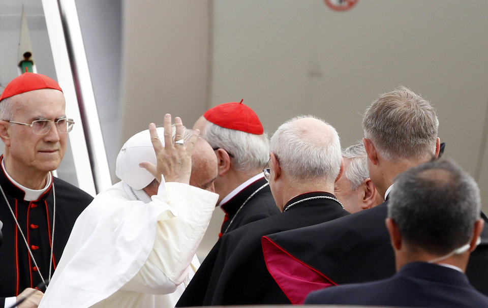 Pope Francis, holds his skull cap as he is welcomed upon his arrival from Rio de Janeiro, Brazil, at Ciampino\'s military airport, on the outskirts of Rome, Monday, July 29, 2013. The pontiff returned after a week in Brazil. At left is Vatican Secretary of State Tarcisio Bertone. (AP Photo/Riccardo De Luca)