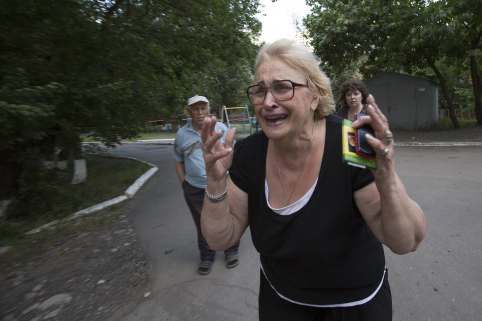 Photo - A woman reacts after seeing the lifeless body of a man killed by shrapnel following a shelling from Ukrainian government forces in Slovyansk, Ukraine, Monday, May 26, 2014. Exit polls from Sunday's first round of the new presidential election predict Petro Poroshenko will be elected president in this bitterly divided country, and he vowed