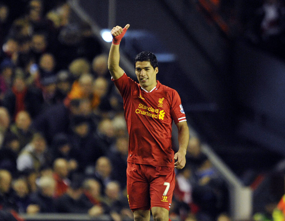 Liverpool's Luis Suarez celebrates after scoring the second goal of the game during their English Premier League soccer match against Norwich City at Anfield in Liverpool, England, Wednesday Dec. 4, 2013. (AP Photo/Clint Hughes)