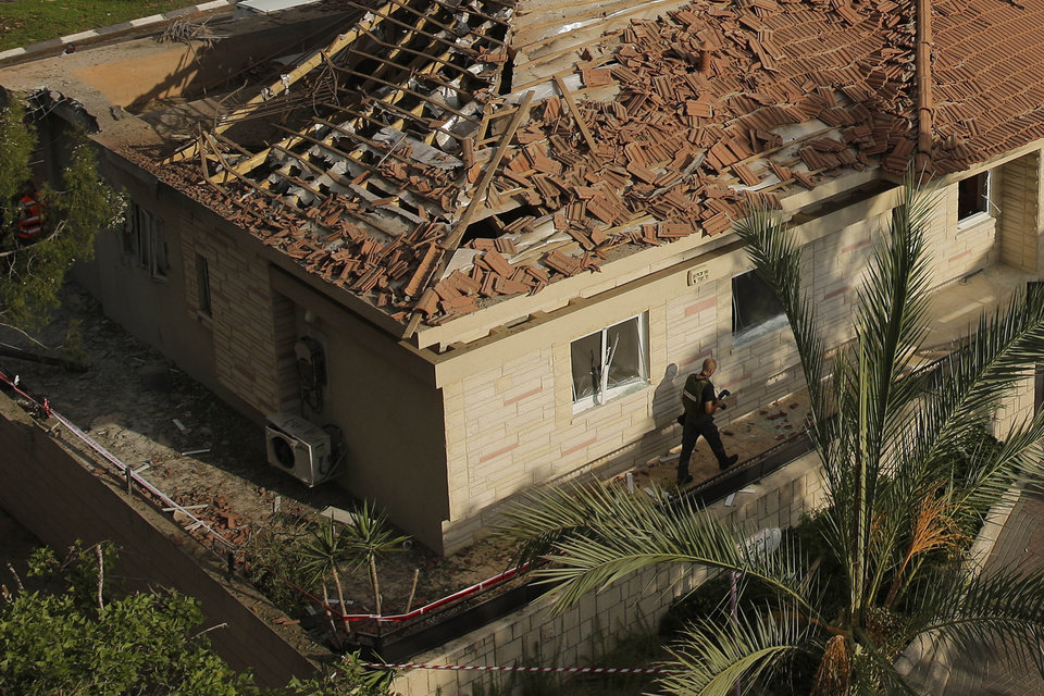 Photo - A police sapper surveys a home hit by a rocket fired from the northern Gaza Strip Tuesday morning in the costal city of Ashkelon, Israel, Tuesday, Aug. 26, 2014. (AP Photo/Tsafrir Abayov)