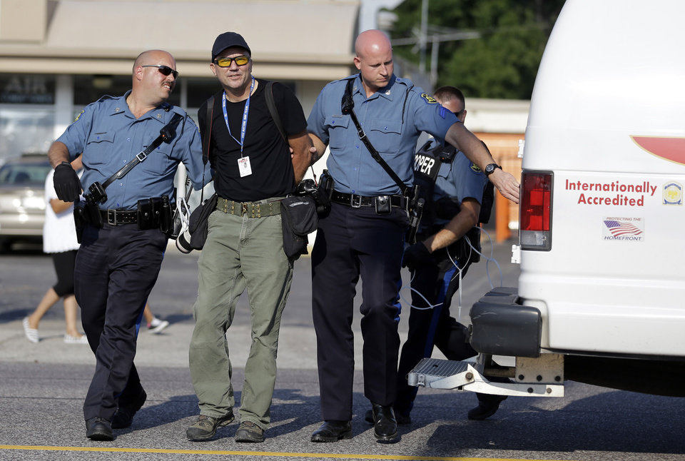 Photo - Getty Images photographer Scott Olson is arrested while covering demonstrators Monday, Aug. 18, 2014, in Ferguson, Mo. Missouri Gov. Jay Nixon called in the National Guard Monday after police again used tear gas to quell protesters in the wake of the shooting of Michael Brown. (AP Photo/Jeff Roberson)
