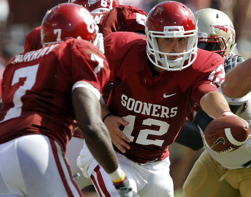 Photo - Oklahoma's Landry Jones (12) hands the ball off to DeMarco Murray (7) during the first half of the college football game between the University of Oklahoma Sooners (OU) and the Florida State University Seminoles (FSU) on Sat., Sept. 11, 2010, in Norman, Okla.  Photo by Chris Landsberger, The Oklahoman
