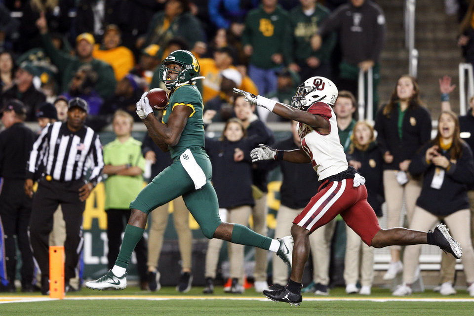 Photo - Baylor wide receiver Denzel Mims (5) catches a touchdown pass over Oklahoma cornerback Jaden Davis (4) during an NCAA college football game, in Waco, Texas, Saturday, Nov. 16, 2019. (Ian Maule/Tulsa World via AP)