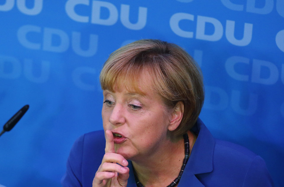 German Chancellor Angela Merkel, chairwoman of the Christian Democratic party CDU, holds a finger on her lips on the stage at the party headquarters after the national elections  in Berlin Sunday, Sept. 22, 2013. Chancellor Angela Merkel's conservatives triumphed in Germany's election Sunday. (AP Photo/Markus Schreiber)