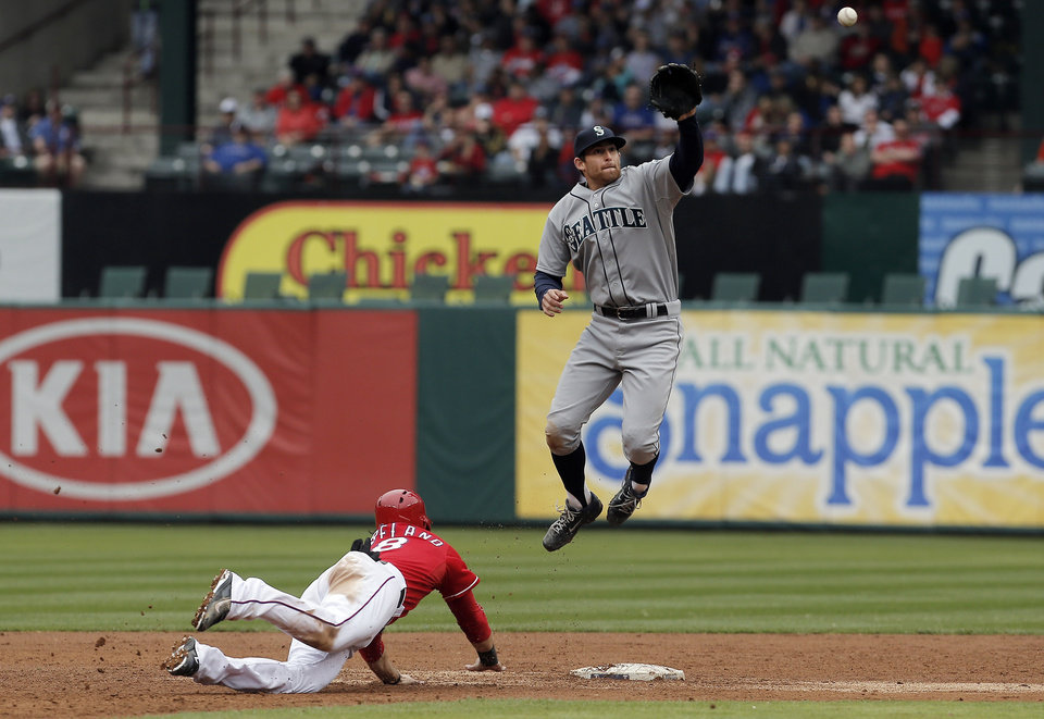 Photo - Texas Rangers Mitch Moreland (18) dives back to second as Seattle Mariners shortstop Brad Miller (5) has to leap in the air to catch the throw from catcher John Buck during the third inning of a baseball game, Thursday, April 17, 2014, in Arlington, Texas. Moreland was safe on the play. (AP Photo/Brandon Wade)