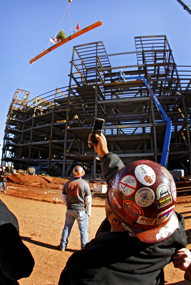 Photo - Dec. 20, 2007: Construction workers look on as the beam that will complete the highest point of the expansion to the Oklahoma State University football stadium is hoisted with a Christmas tree mounted to it during the