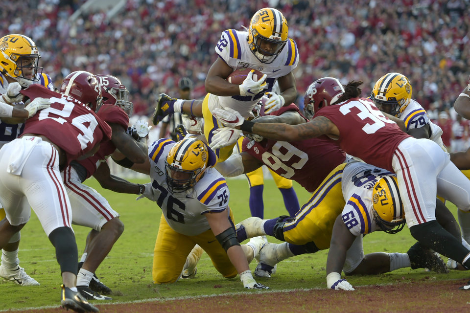 Photo - LSU running back Clyde Edwards-Helaire (22) dives over Alabama's Raekwon Davis (99) and Markail Benton (36) to score a touchdown in the first half of an NCAA college football game, Saturday, Nov. 9, 2019, in Tuscaloosa, Ala. (AP Photo/Vasha Hunt)