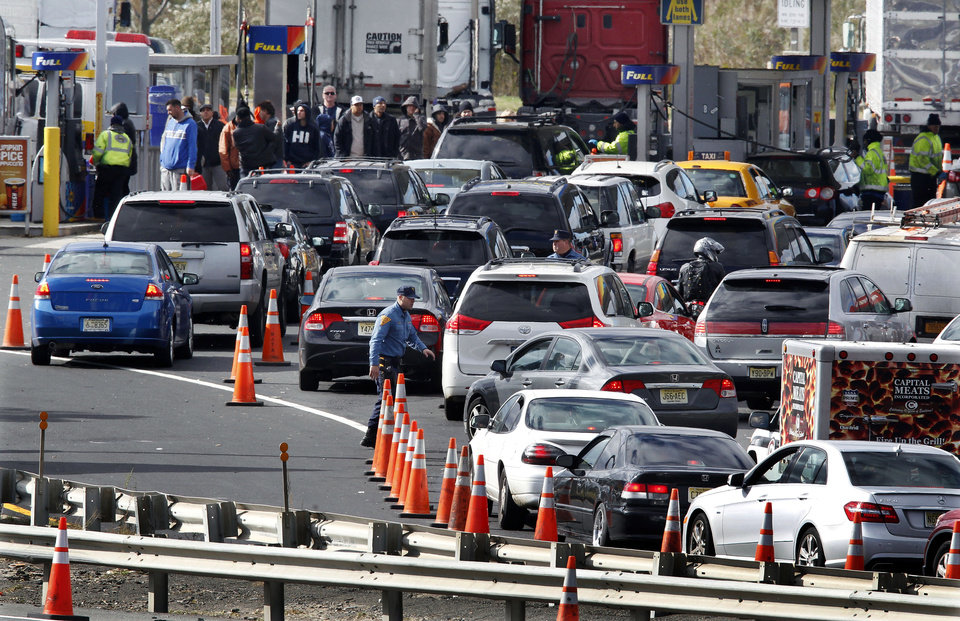 Photo -   New Jersey state troopers keep order as motorists line up to purchase gasoline at the Thomas A. Edison service area on the New Jersey Turnpike, Saturday, Nov. 3, 2012, near Woodbridge, N.J. Gas lines were long at some gas stations Saturday morning with motorists trying to make purchases before a noon switch to a gas rationing system ordered by Gov. Chris Christie. Drivers with license plates ending in an even number will be allowed to buy gas on even-numbered days, and those with plates ending in an odd number can make gas purchases on odd-numbered days. Christie says it will help ease fuel shortages and extended lines for gasoline that have occurred since Superstorm Sandy decimated the coast. (AP Photo/Mel Evans)