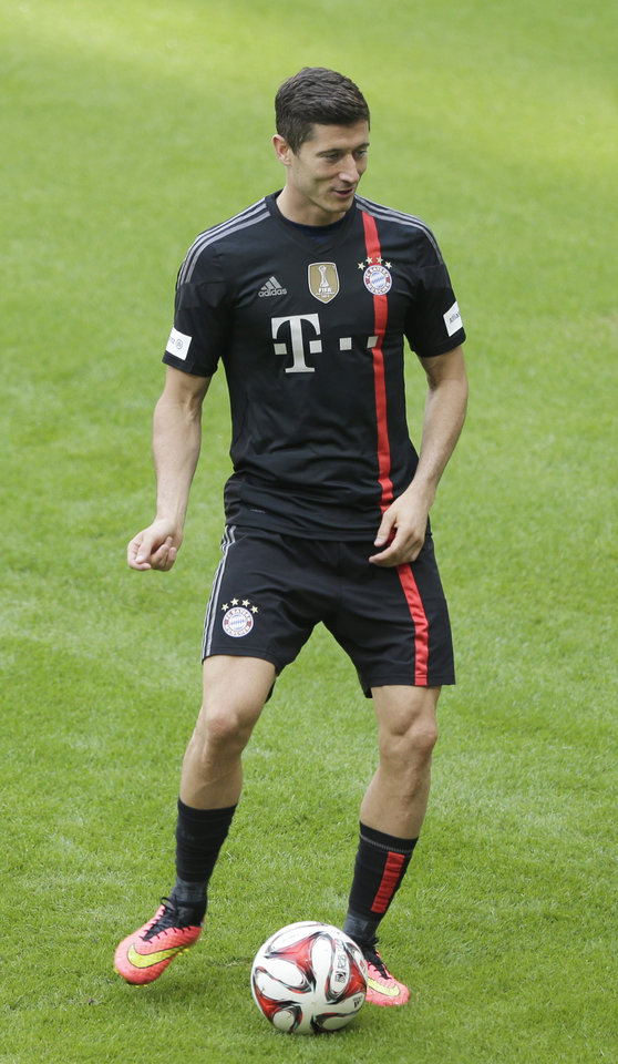 Photo - Bayern Munich's Robert Lewandowski of Poland kicks a ball during a training session after an official team presentation in the Allianz Arena stadium for the new German first division Bundesliga soccer season, in Munich, southern Germany, Saturday, Aug. 9, 2014. 65,000 spectators attended the event. (AP Photo/Matthias Schrader)