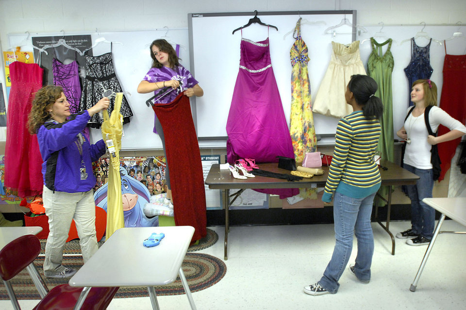 Photo -   In this photo taken Oct. 2, 2012 in Bloomington, Ill., from left, English teacher and senior advisor Gloria McElwain, helps her daughter, Ginny McElwain, 17, a senior, Kiara Cross, 16, and Alexandra Furoman, 16, both juniors, as they set up prom dresses for Bloomington High School's House of Style. The House of Style started four years ago when advisor McElwain, urged a student to go to the prom who said she couldn't afford a dress. McElwain was not deterred by the students predicament and got the girl a dress and she went to the dance. Since then McElwain and various volunteers have given away 370 dresses to BHS students for homecoming and prom dances, even weddings. (AP Photo/The Pantagraph, David Proeber)