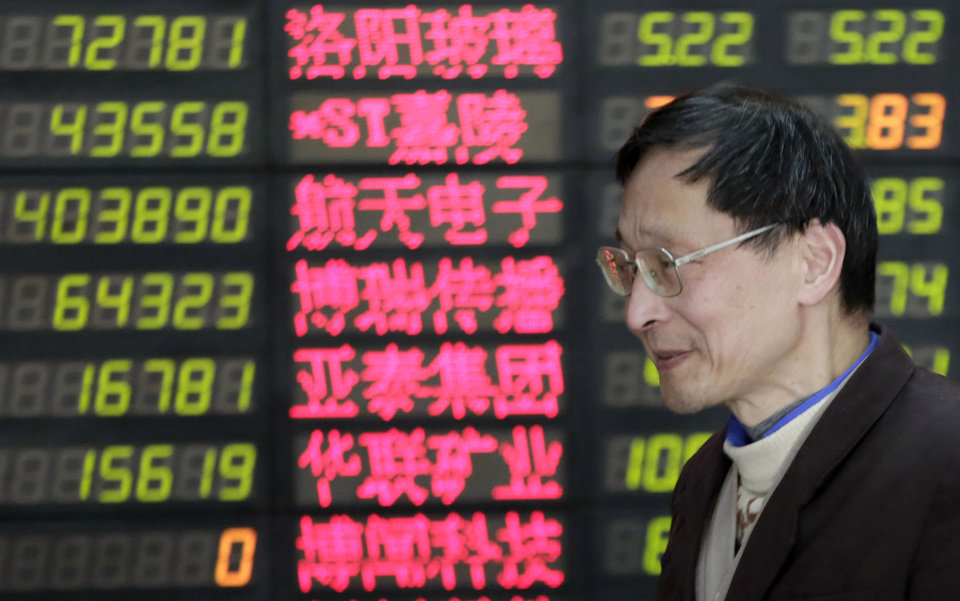 An investor looks at the stock price monitor at a private securities company on Thursday, March 28, 2013, in Shanghai, China. Renewed jitters about the debt crisis in Europe sent Asian stock markets lower Thursday. (AP Photo/Eugene Hoshiko)