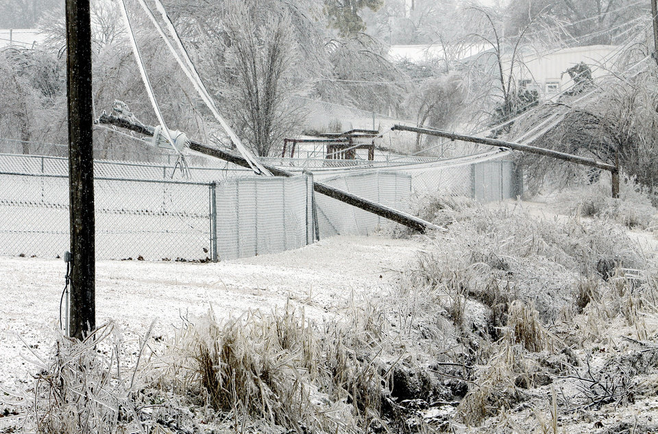 Photo - Power poles lay over fences on Friday, Jan. 29, 2010, in Purcell, Okla. after a winter storm.  Photo by Steve Sisney, The Oklahoman