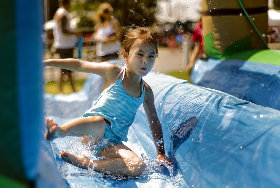 Keira Nguyen, 4, cools off on the water slide during the Yukon Freedom Fest at the Yukon City Park on Thursday , July 4, 2013, in Yukon, Okla. Photo by Chris Landsberger, The Oklahoman