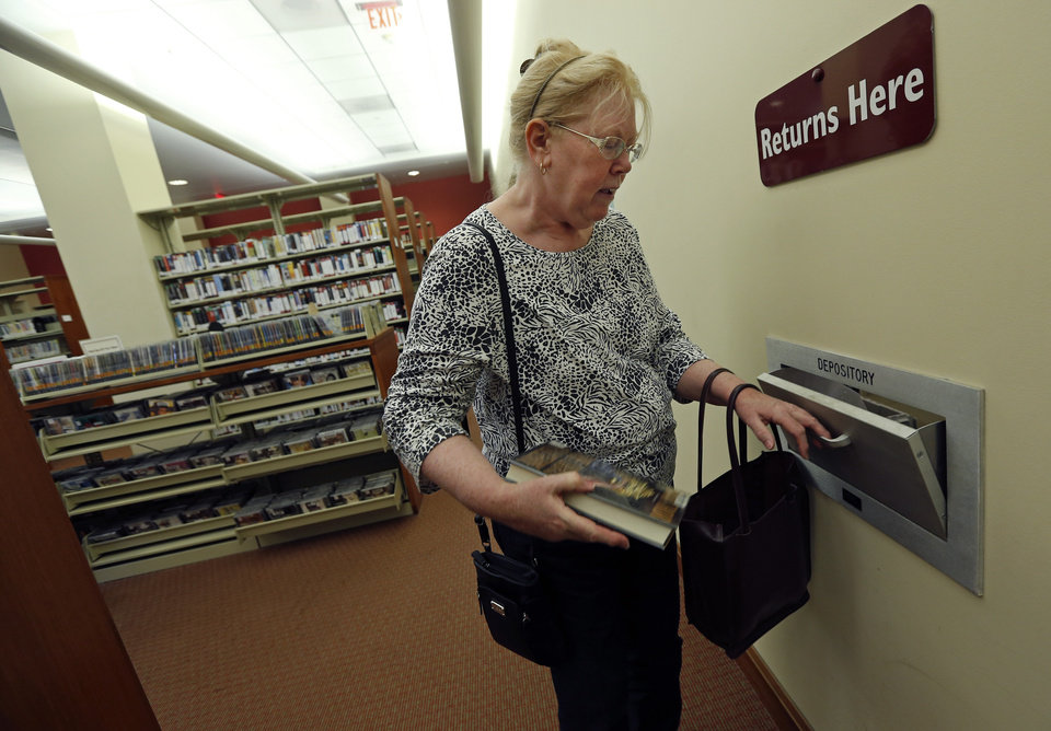Photo -  In this July 7 photo, Susan McNamara returns a book to the public library in Quincy, Mass.AP Photo   Elise Amendola -  AP