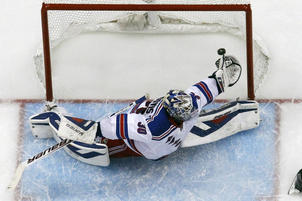 Photo - A shot by Pittsburgh Penguins' Jussi Jokinen gets past the glove hand of New York Rangers goalie Henrik Lundqvist (30) in the third period of game 2 of a second-round NHL playoff hockey series against the New York Rangers in Pittsburgh Sunday, May 4, 2014. The Penguins won 3-0, to tie the series at 1-1. (AP Photo/Gene J. Puskar)