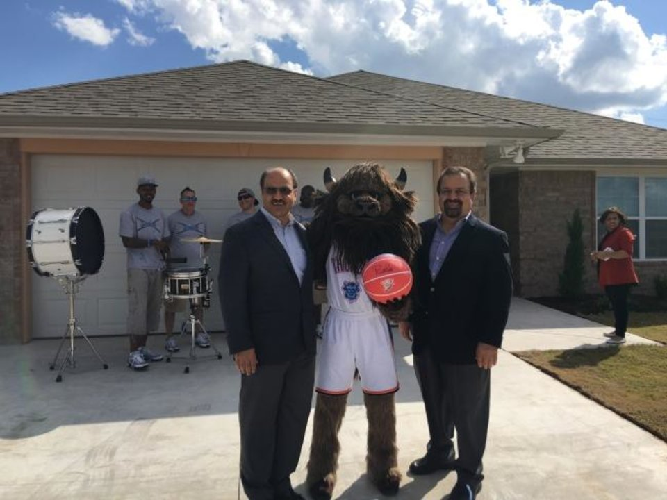 Photo -  Jalal and Mohammed Farzaneh are shown with OKC Thunder mascot Rumble, at a home the brothers, owners of Home Creations, donated to Central Oklahma Habitat For Humanity. [PHOTO PROVIDED]