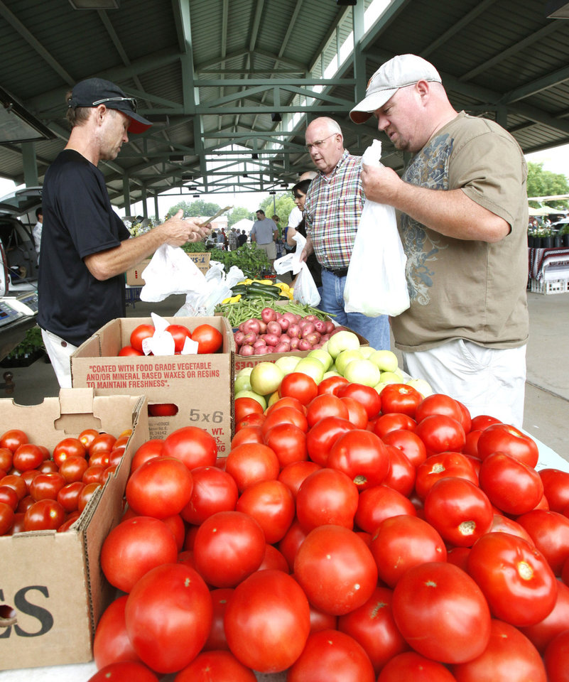 Photo - Johnny Houzvicka, right, purchases vegetables from Cole Hayhurst, with Hayhurst Farms, on the opening day at Edmond Farmers Market. PHOTO BY PAUL HELLSTERN, THE OKLAHOMAN.  PAUL HELLSTERN - OKLAHOMAN