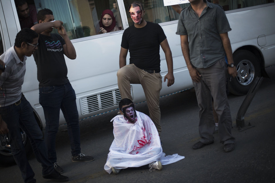 Photo - An Egyptian youth wearing a mask of Hosni Mubarak steps on a comrade covered with a fake blood-stained shroud while performing during a protest against the release of former Egypt's dictator in Qasr Al-Nil bridge, in downtown Cairo, Egypt, Thursday, Aug. 22, 2013. (AP Photo/Manu Brabo)