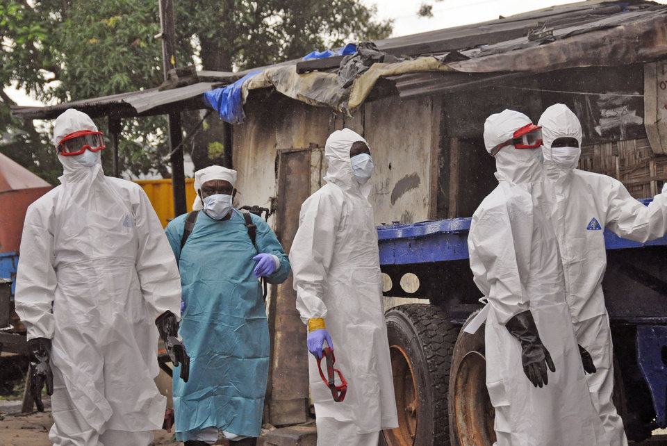 Photo - Liberian health workers outside a home of a man that they believed died from the Ebola virus in Monrovia, Liberia, Friday, Aug. 29, 2014.  The Ebola outbreak in West Africa eventually could exceed 20,000 cases, more than six times as many as are now known, the World Health Organization said Thursday. A new plan released by the U.N. health agency to stop Ebola also assumes that the actual number of cases in many hard-hit areas may be two to four times higher than currently reported.(AP Photo/Abbas Dulleh)