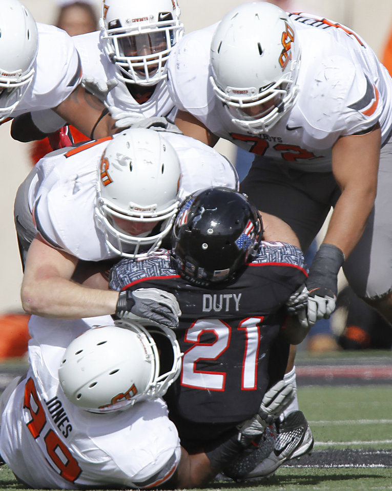 The Oklahoma State defense brings down Texas Tech Red Raiders running back DeAndre Washington (21) during the college football game between the Oklahoma State University Cowboys (OSU) and Texas Tech University Red Raiders (TTU) at Jones AT&T Stadium on Saturday, Nov. 12, 2011. in Lubbock, Texas.  Photo by Chris Landsberger, The Oklahoman  ORG XMIT: KOD