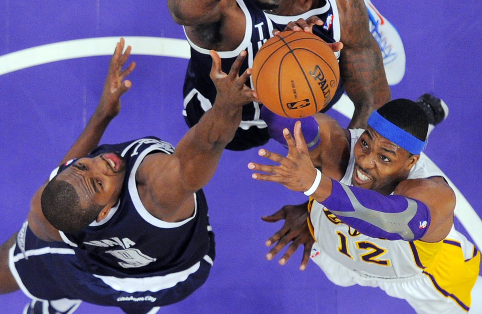 Photo - Oklahoma City Thunder power forward Serge Ibaka (9), of the Republic of Congo, and Los Angeles Lakers center Dwight Howard (12) reach for a rebound during the first half of their NBA basketball game, Sunday, Jan. 27, 2013, in Los Angeles. The Lakers won 105-96. (AP Photo/Reed Saxon)