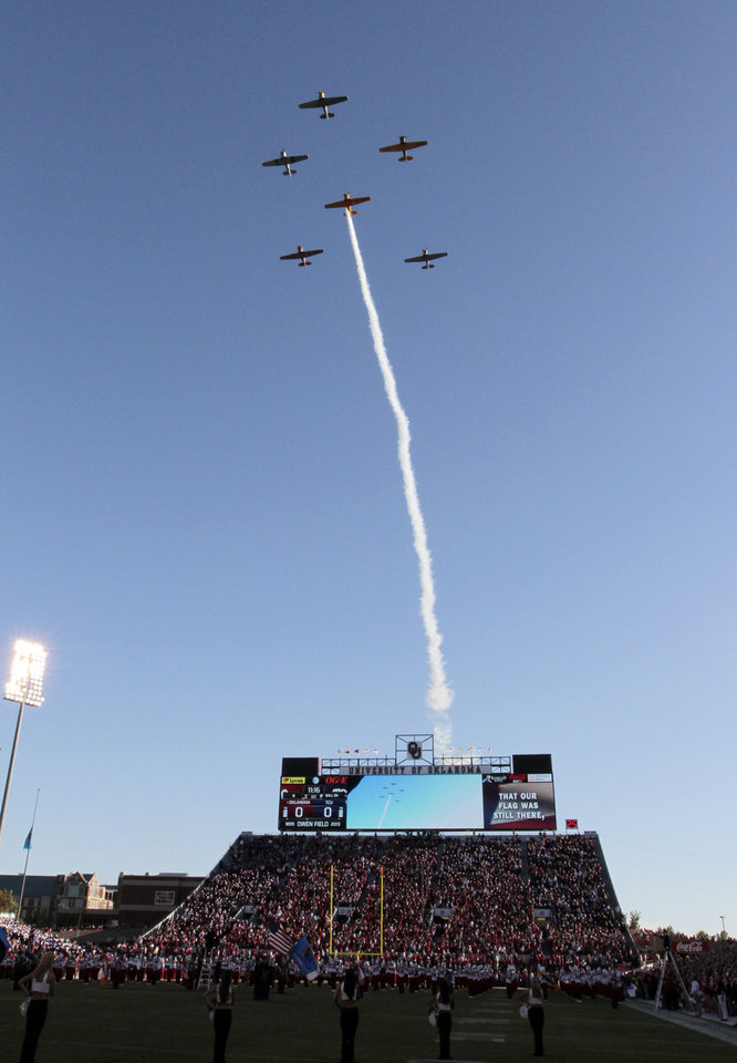 Photo - Warbirds fly their vintage airplanes during the pre game of a college football game between the University of Oklahoma Sooners (OU) and the TCU Horned Frogs at Gaylord Family-Oklahoma Memorial Stadium in Norman, Okla., on Saturday, Oct. 5, 2013. Photo by Steve Sisney, The Oklahoman