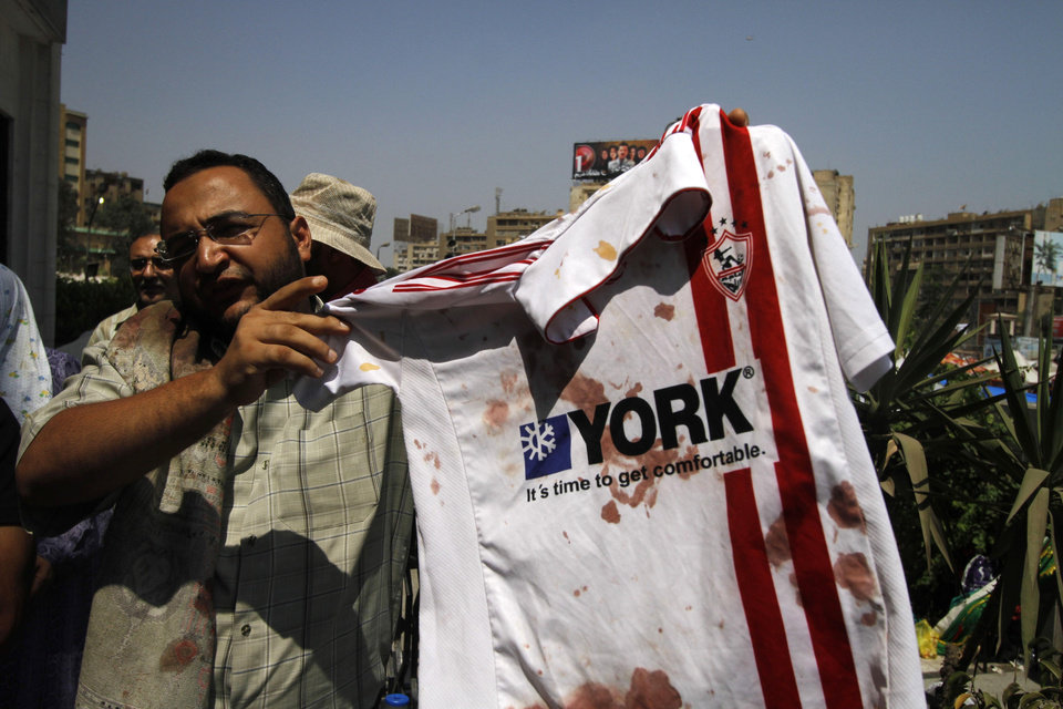 Photo - A supporter of ousted Egyptian President Mohammed Morsi stands outside a local hospital in Cairo holding a bloodied shirt he says belongs to a protester shot by soldiers during a demonstration, Monday, July 8, 2013. Egyptian soldiers and police opened fire on supporters of the ousted president early Monday in violence that left dozens of people killed, including one officer, outside a military building in Cairo where demonstrators had been holding a sit-in, government officials and witnesses said. (AP Photo/Nasser Shiyoukhi)