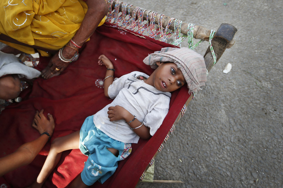 Photo - A young Indian boy, suffering from fever, lies on a cot at a makeshift tent provided by the government for people displaced by floods along the banks of the Yamuna River, in New Delhi, India, Friday, June 21, 2013. Although the water level in the Yamuna receded below danger levels, for many it will be sometime yet before they can return home in the low lying areas along the riverbank and resume regular life. (AP Photo/Saurabh Das)