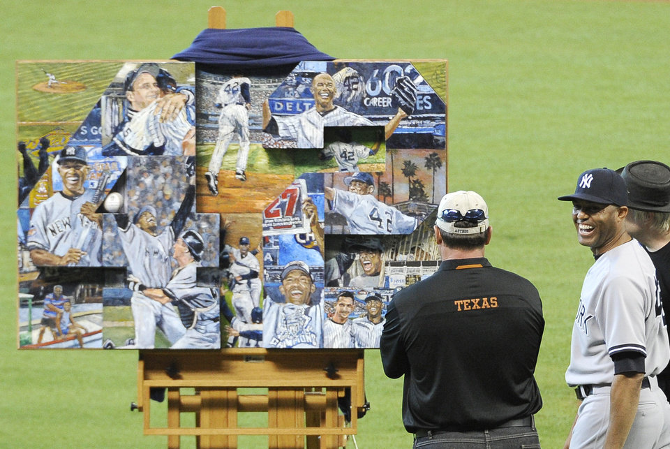 Photo - New York Yankees relief pitcher Mariano Rivera, right, smiles at former Yankees pitcher Roger Clemens, left, as they look at the painting presented to Rivera to honor his 18-year career in baseball game Sunday, Sept. 29, 2013, in Houston. (AP Photo/Pat Sullivan)