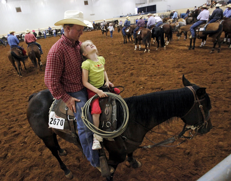 Lauren Barton, 6, sits on quarter horse Big Smoking Otoe with her father, James Barton, while waiting for his chance to compete in roping during the Battle in the Saddle at the State Fair Park in Oklahoma City, Thursday, July 5, 2012. Photo by Nate Billings, The Oklahoman