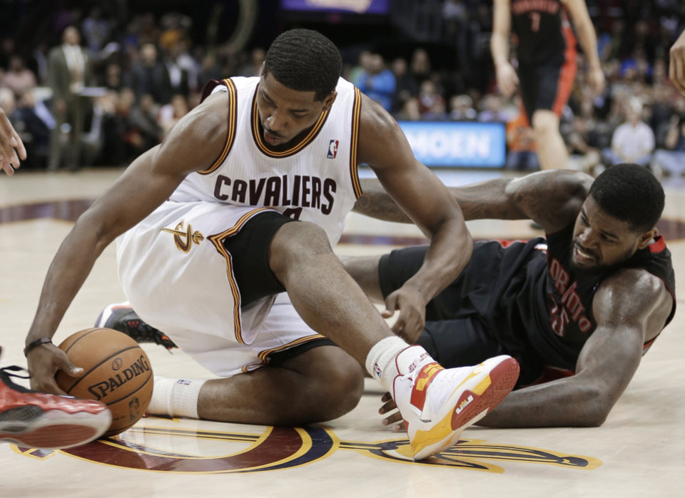 Photo - Cleveland Cavaliers' Tristan Thompson, left, and Toronto Raptors' Amir Johnson scramble for a loose ball during the fourth quarter of an NBA basketball game Wednesday, Feb. 27, 2013, in Cleveland. The Cavaliers won 103-92. (AP Photo/Tony Dejak)