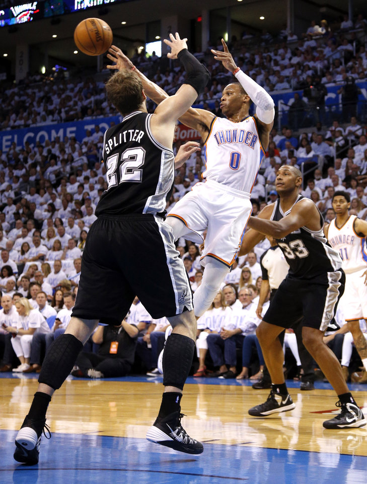 Photo - Oklahoma City's Russell Westbrook (0) passes the ball in between San Antonio's Tiago Splitter (22) and Boris Diaw (33) during Game 6 of the Western Conference Finals in the NBA playoffs between the Oklahoma City Thunder and the San Antonio Spurs at Chesapeake Energy Arena in Oklahoma City, Saturday, May 31, 2014. Photo by Bryan Terry, The Oklahoman