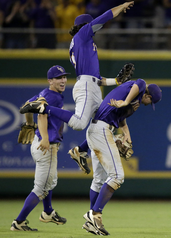 Photo - LSU infielder Kramer Robertson leaps on outfielder Andrew Stevenson as they celebrate with infielder Alex Bregman, left, after their 5-1 victory over Houston during an NCAA college baseball regional tournament game in Baton Rouge, La., Saturday, May 31, 2014. (AP Photo/Gerald Herbert)