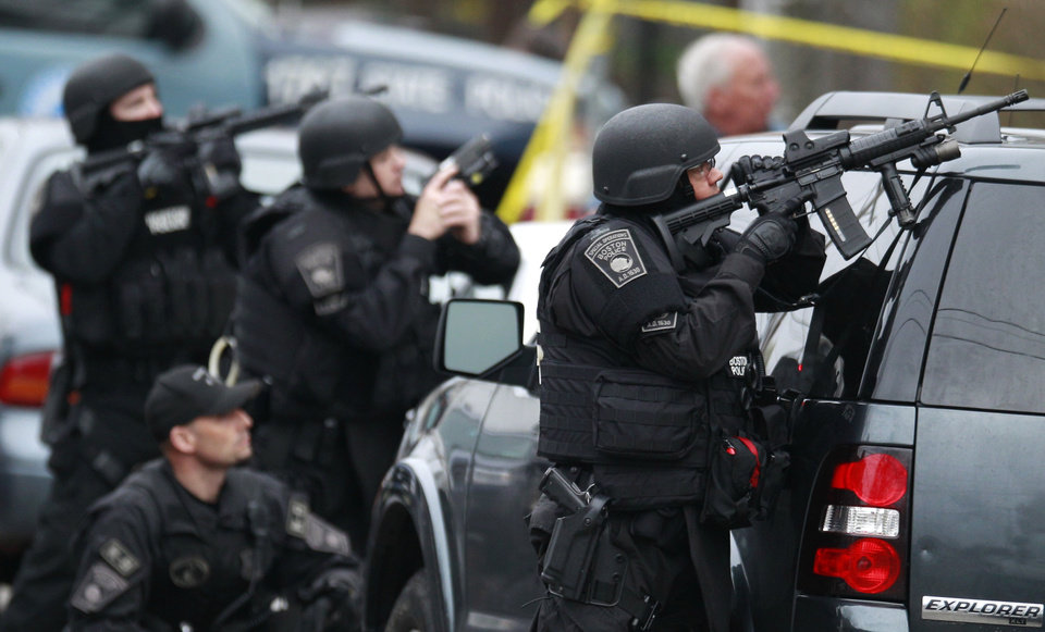 Photo - Police in tactical gear surround an apartment building while looking for a suspect in the Boston Marathon bombings in Watertown, Mass., Friday, April 19, 2013. The bombs that blew up seconds apart near the finish line of the Boston Marathon left the streets spattered with blood and glass, and gaping questions of who chose to attack and why. (AP Photo/Charles Krupa)