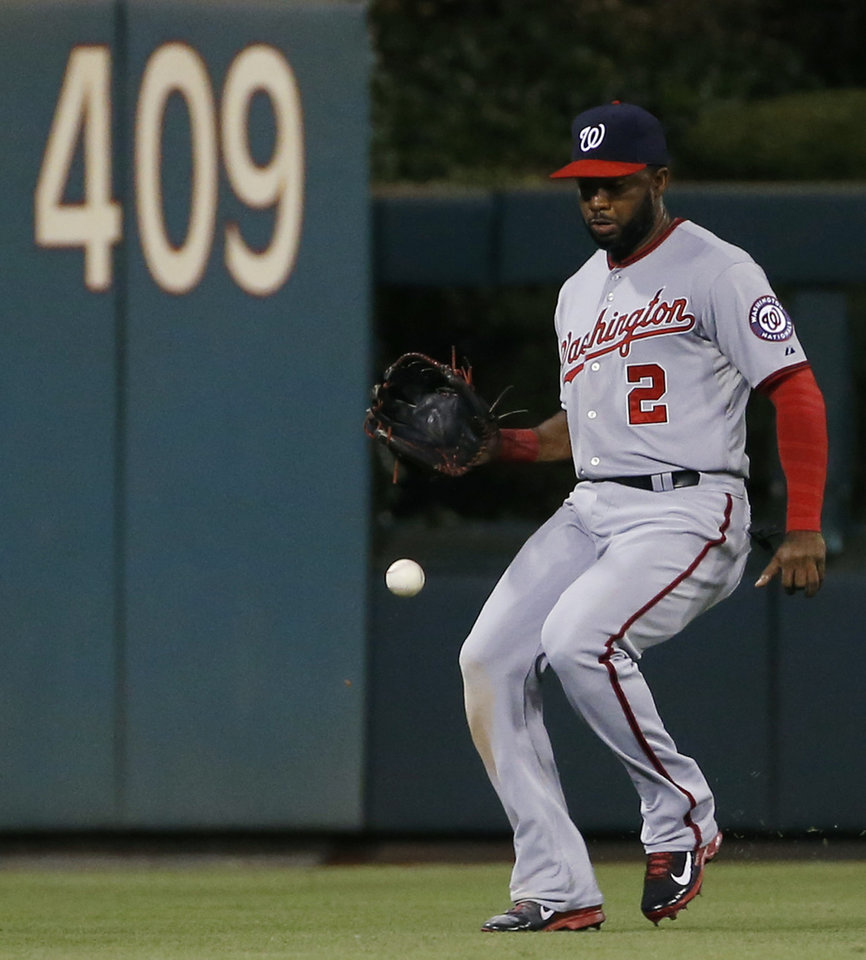 Photo - Washington Nationals center fielder Denard Span misplays a single by Philadelphia Phillies' Ryan Howard during the first inning of a baseball game, Wednesday, Aug. 27, 2014, in Philadelphia. Howard reached second base on the error by Span. (AP Photo/Matt Slocum)