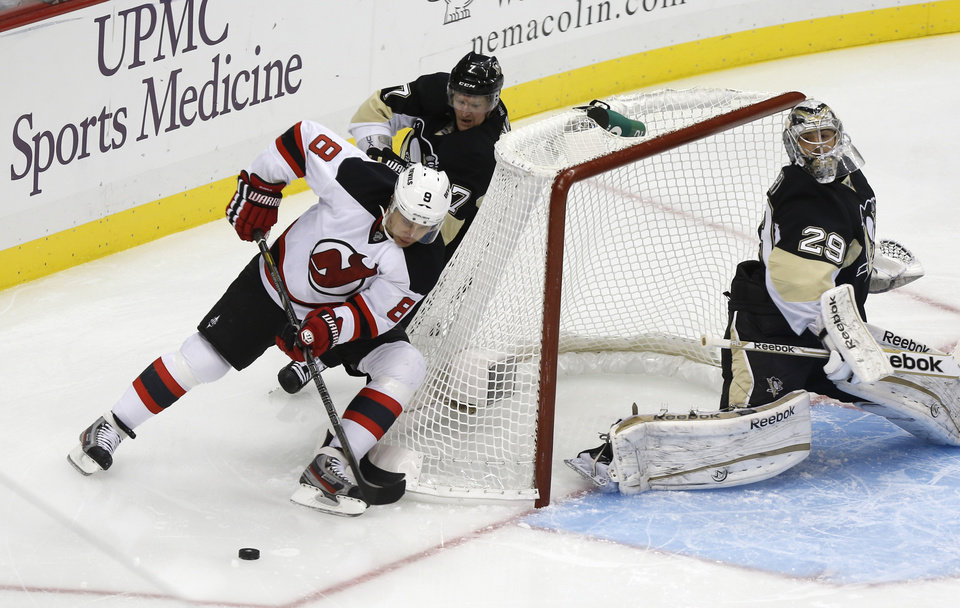 New Jersey Devils\' Dainius Zubrus (8) brings the puck around the net in front of Pittsburgh Penguins\' Paul Martin (7) as goalie Marc-Andre Fleury (29) watches during the first period of an NHL hockey game, Saturday, Feb. 2, 2013, in Pittsburgh. (AP Photo/Keith Srakocic)
