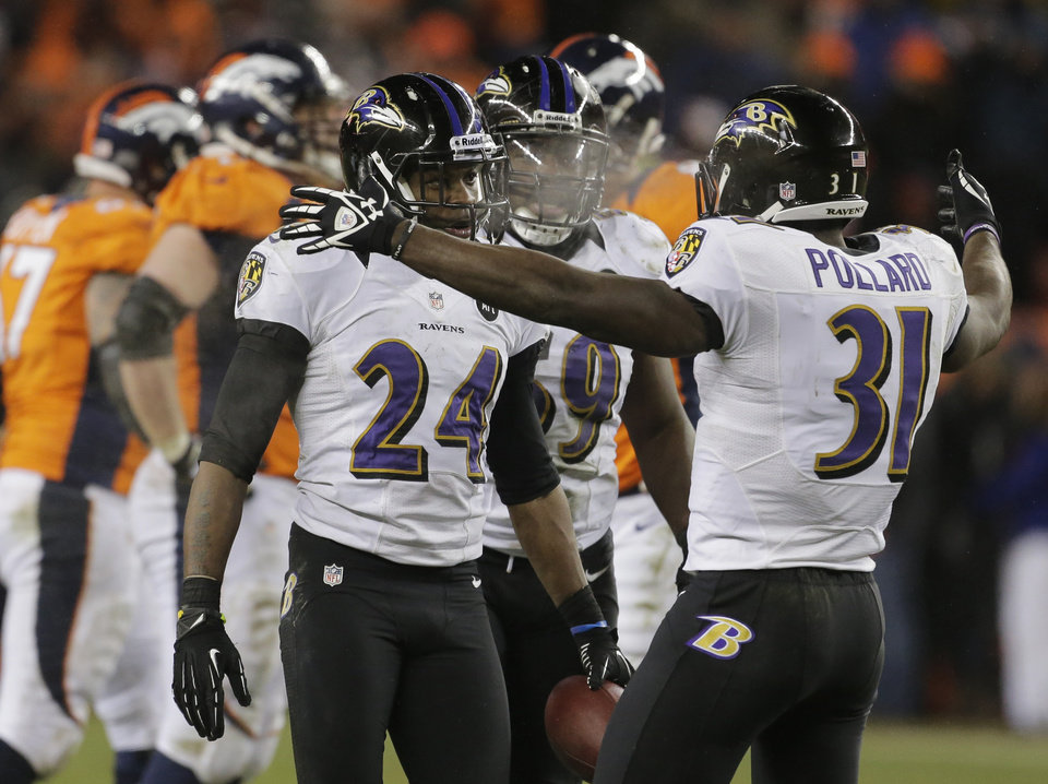 Photo - Baltimore Ravens cornerback Corey Graham (24) is congratulated by Baltimore Ravens strong safety Bernard Pollard (31) after intercepting a pass against the Denver Broncos in overtime of an AFC divisional playoff NFL football game, Saturday, Jan. 12, 2013, in Denver. The Ravens won 38-35. (AP Photo/Charlie Riedel)