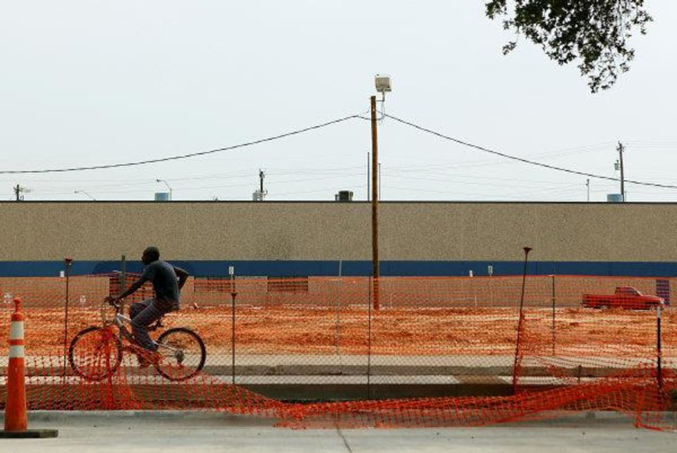 A man rides his bike past the recommended site for the proposed convention center west of the Oklahoma City Arena on Reno in Oklahoma City. Photo by John Clanton, The Oklahoman John Clanton
