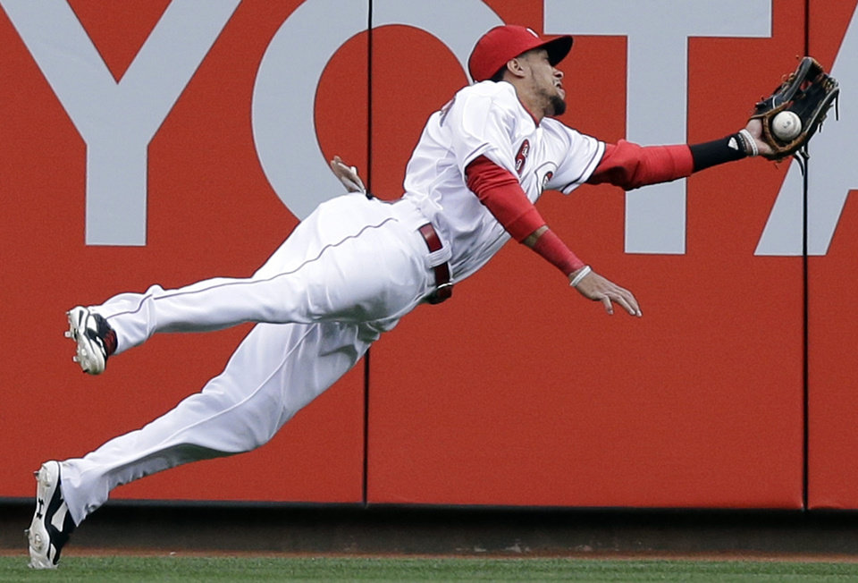 Photo - Cincinnati Reds center fielder Billy Hamilton makes a diving catch on a fly ball hit by Milwaukee Brewers' Carlos Gomez in the first inning of a baseball game, Thursday, May 1, 2014, in Cincinnati. (AP Photo/Al Behrman)