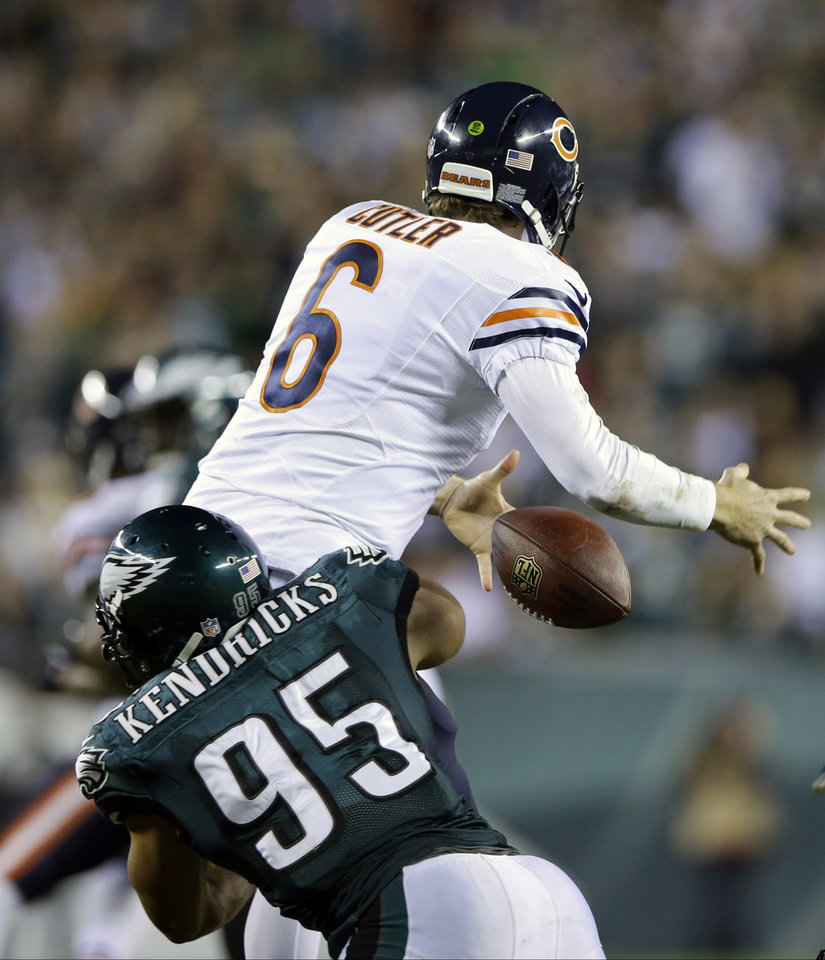 Photo - Chicago Bears' Jay Cutler (6) fumbles the ball as he is hit by Philadelphia Eagles' Mychal Kendricks (95) during the second half of an NFL football game, Sunday, Dec. 22, 2013, in Philadelphia. (AP Photo/Michael Perez)