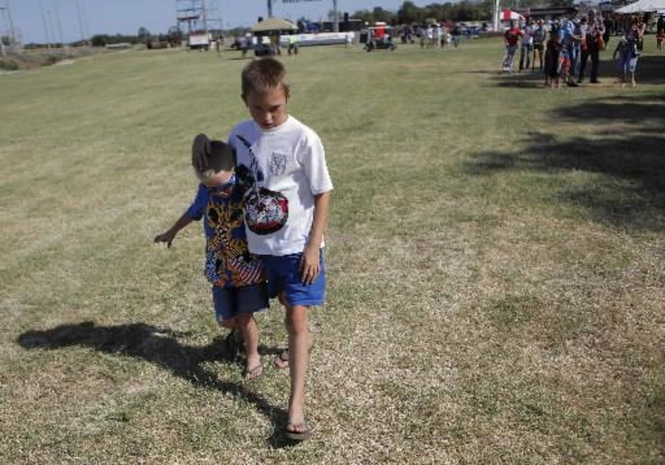 Photo - Chase Brooks, 9, of Maud, walks with his cousin, Joseph Brooks, 5, at a Fourth of July Celebration in Seminole, Okla., July 4, 2012. Photo by Garett Fisbeck, The Oklahoman