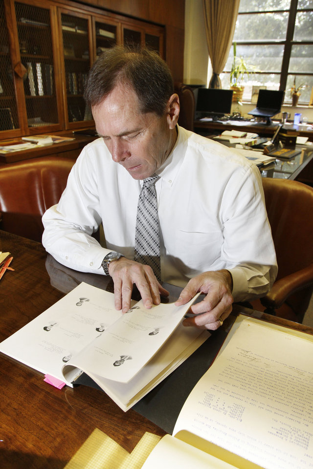 Photo - Oklahoma City Public Schools Superintendent Karl Springer looks at a 1911 Central High School yearbook in his office in Oklahoma City, Tuesday, July 3, 2012. Photo By Steve Gooch, The Oklahoman