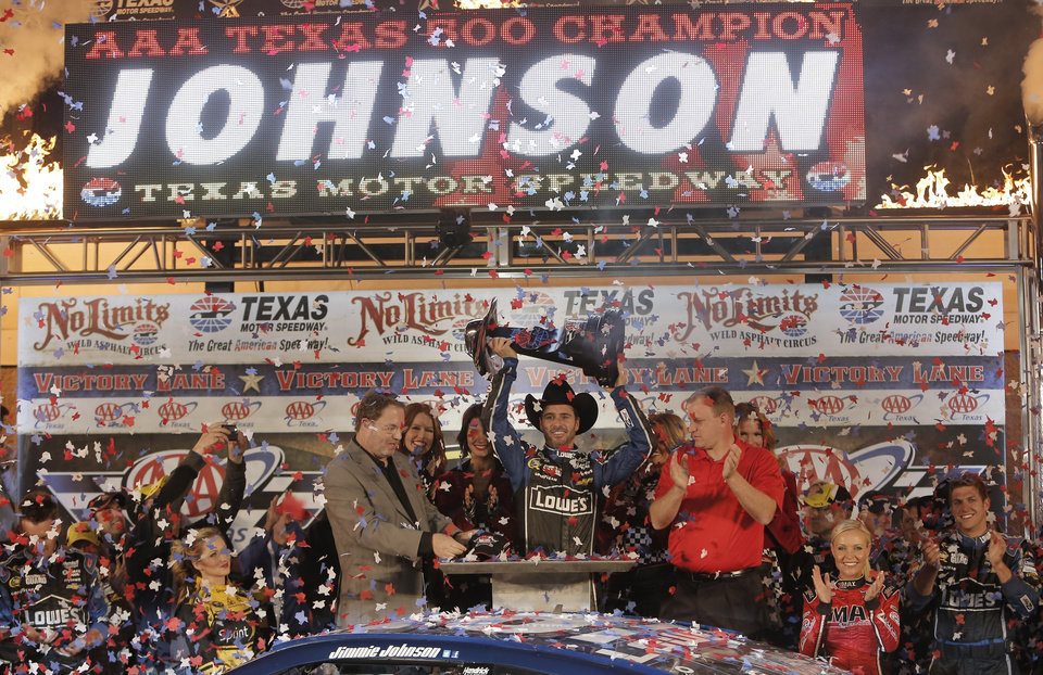 Photo - Jimmie Johnson (48) celebrates winning the NASCAR Sprint Cup series auto race at Texas Motor Speedway in Fort Worth, Texas, Sunday, Nov. 3, 2013. (AP Photo/Brandon Wade)